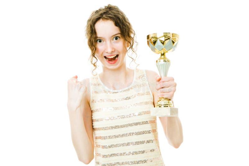 Jeune fille joyeuse de champion tenant le troph?e de gain image libre de droits