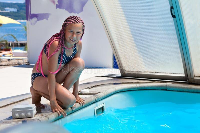 Jeune fille joyeuse et souriante prête à sauter dans l'eau bleue de la piscine, dreadlocks roses, peau bronzée photos libres de droits