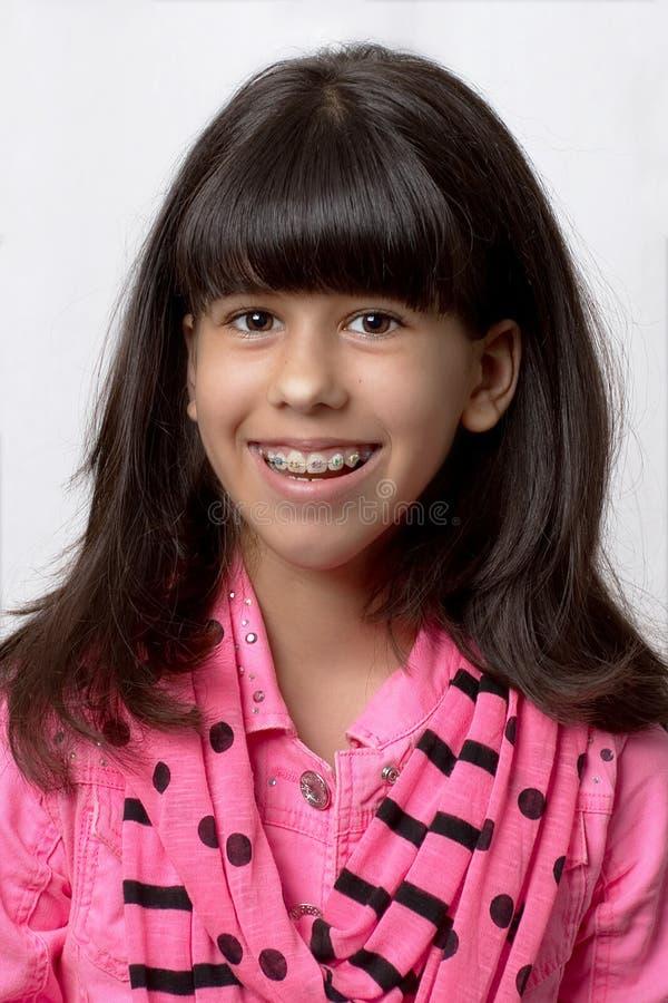Jeune fille latine souriant avec les accolades colorées photographie stock