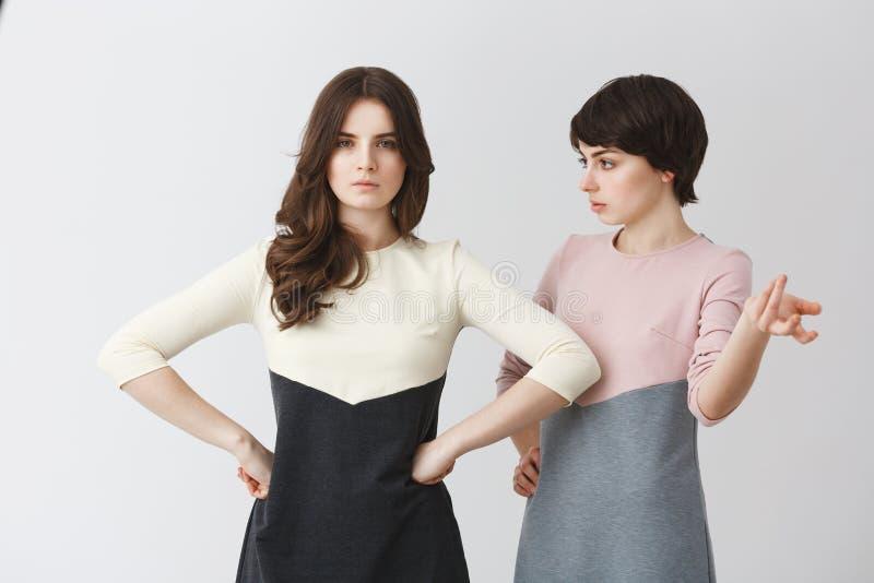 Jeune fille lesbienne belle d'étudiant discutant avec sa belle amie aux cheveux longs au sujet de la meilleure pose pour la photo photographie stock libre de droits