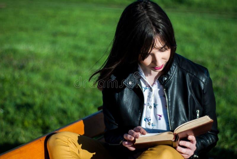 Jeune fille lisant un livre un jour ensoleillé de ressort sur un banc en nature images stock