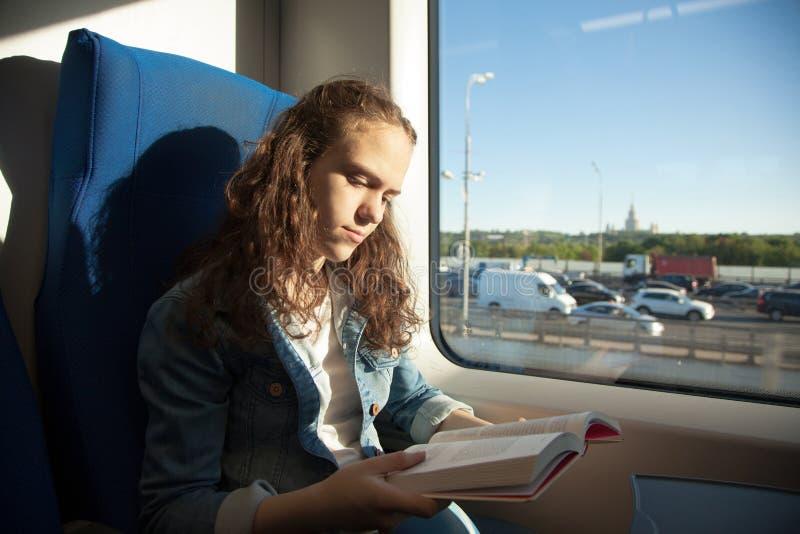 Jeune fille lisant un livre tandis que sur un train à une lumière du soleil photo stock