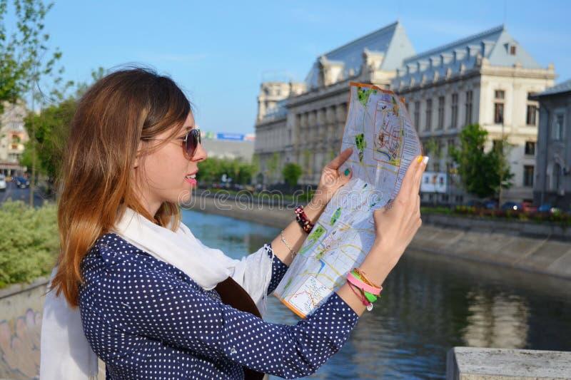 Jeune fille lisant une carte près d'une rivière photos stock