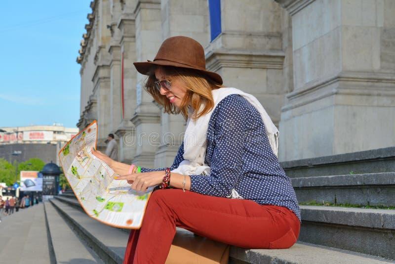 Jeune fille lisant une carte se reposant sur un escalier image libre de droits