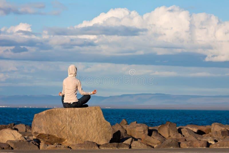 Jeune fille méditant par la mer photos stock