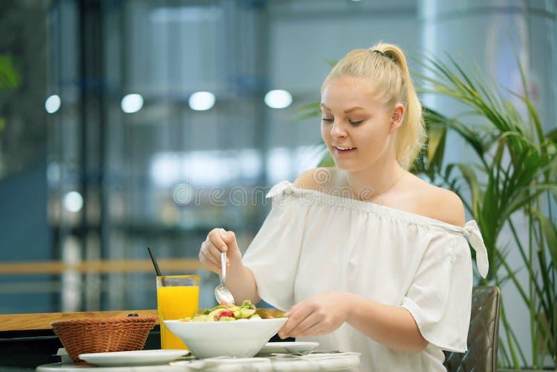 Jeune fille mangeant de la salade dans un café image stock
