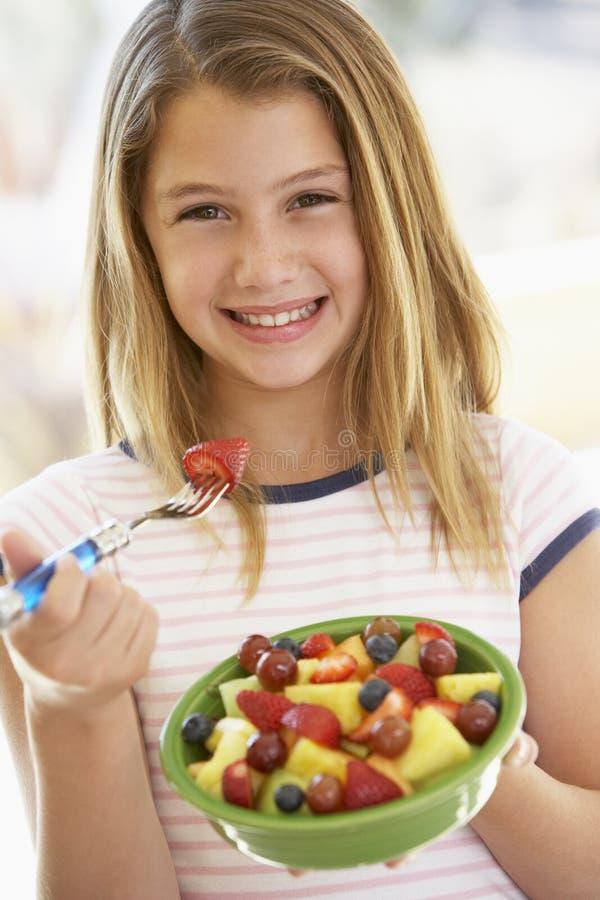 Jeune fille mangeant de la salade de fruits fraîche images libres de droits