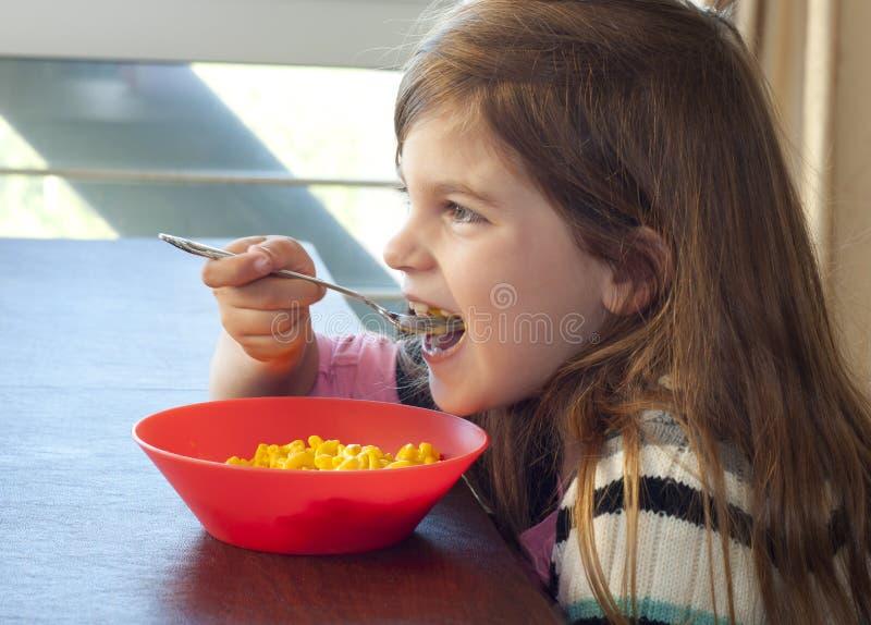 Jeune fille mangeant des macaronis et du fromage images stock