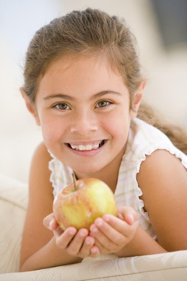 Jeune fille mangeant la pomme dans le sourire de salle de séjour photographie stock