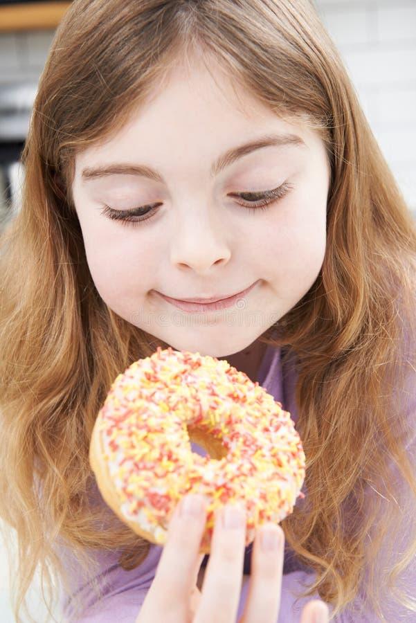 Jeune fille mangeant le beignet sucré pour le casse-croûte photo libre de droits