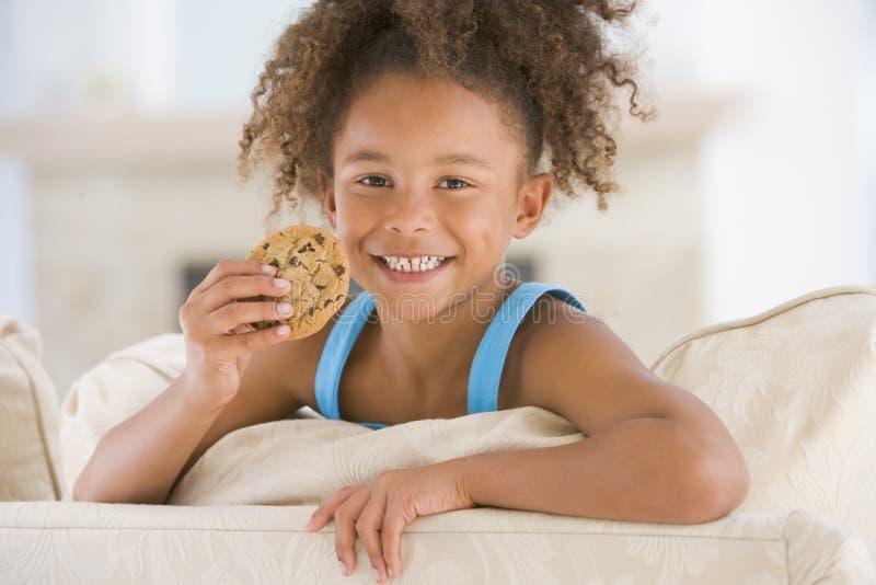Jeune fille mangeant le biscuit dans le sourire de salle de séjour image libre de droits