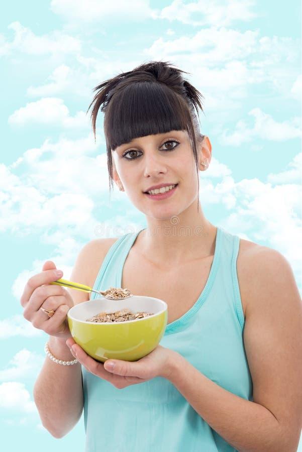 Jeune fille mangeant le bol de céréale de petit déjeuner saine photographie stock