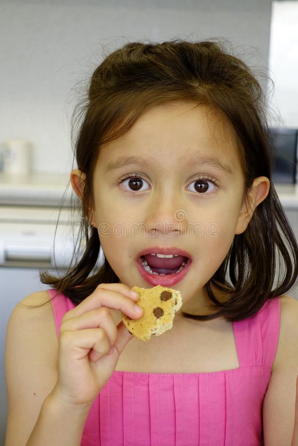 Jeune fille mangeant un Bicsuit. photographie stock libre de droits
