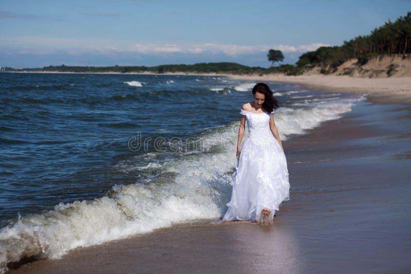 Jeune fille marchant le long du bord de la mer image libre de droits