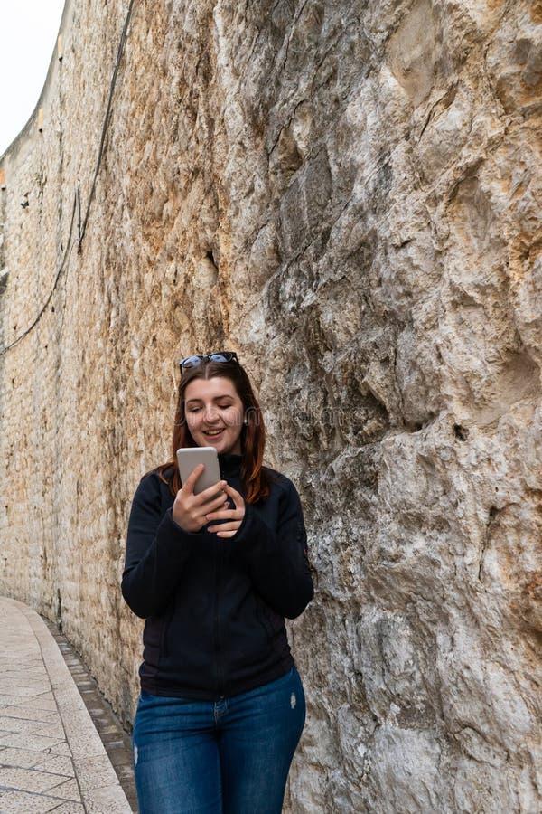 Jeune fille marchant par les rues étroites antiques et dactylographiant un téléphone intelligent Belle femme principale rouge par photographie stock