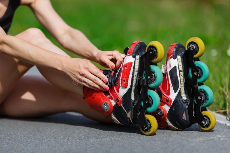 Jeune fille mettant sur les patins intégrés photographie stock