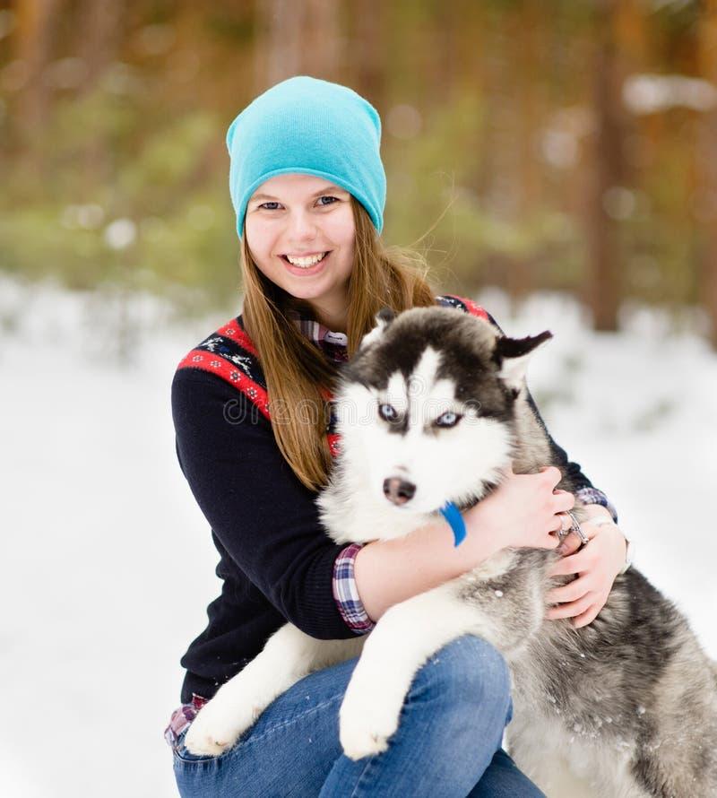 Jeune fille mignonne avec le chien hasky dans la forêt d'hiver photographie stock libre de droits