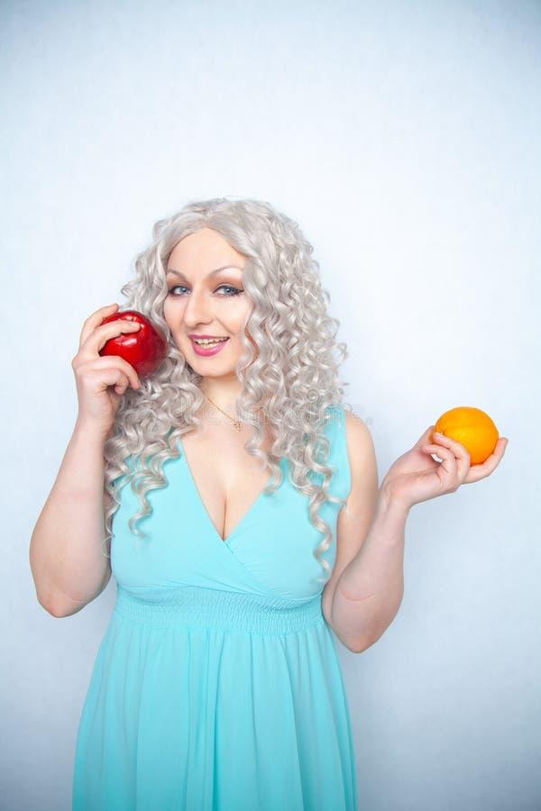 Jeune fille mignonne avec les cheveux blancs bouclés et le fruit de pomme de participation de figure et orange dodu sur le fond d photos libres de droits