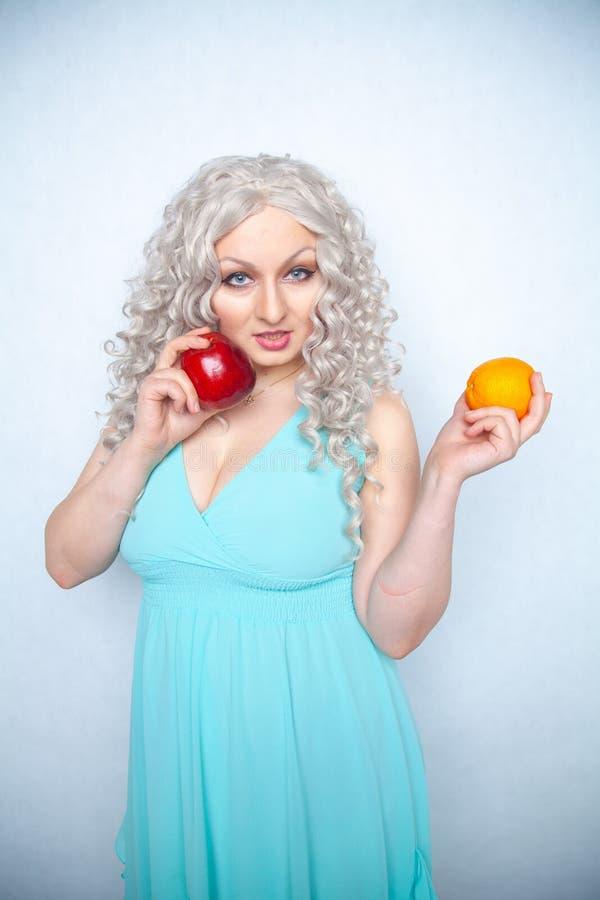 Jeune fille mignonne avec les cheveux blancs bouclés et le fruit de pomme de participation de figure et orange dodu sur le fond d images libres de droits