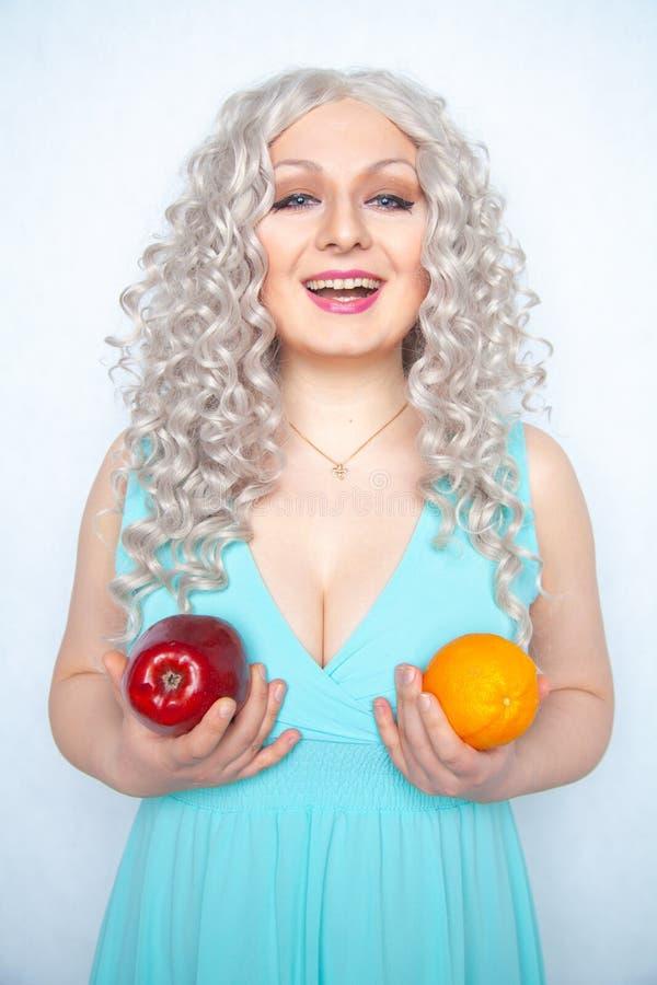 Jeune fille mignonne avec les cheveux blancs bouclés et le fruit de pomme de participation de figure et orange dodu sur le fond d photo stock