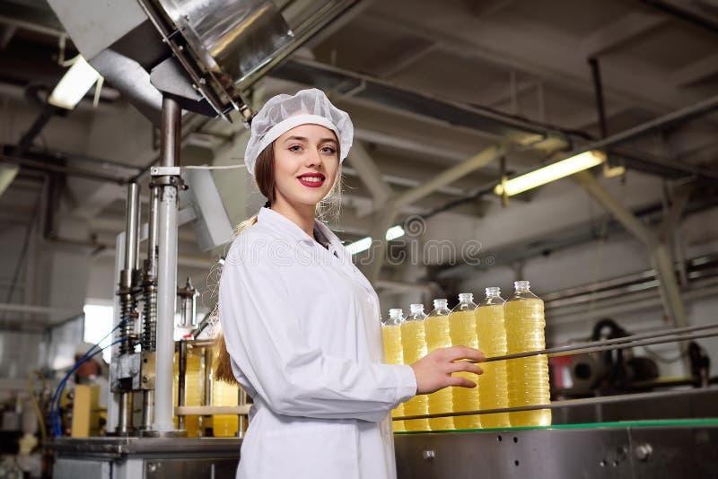Jeune fille mignonne avec une bouteille de tournesol ou d'huile d'olive photographie stock libre de droits