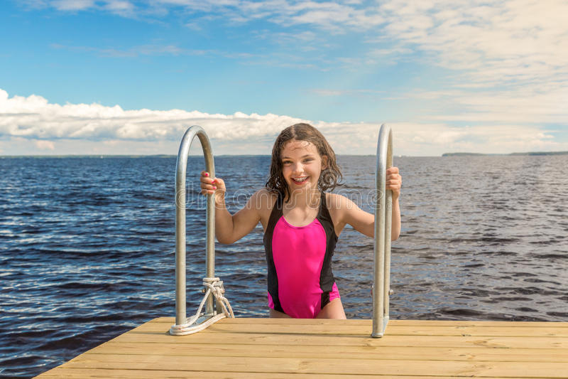 Jeune fille mignonne dans le maillot de bain riant, dehors l'été de pont images libres de droits