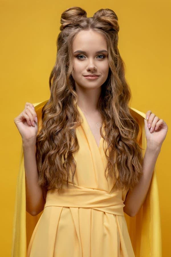 Jeune fille mignonne dans une robe jaune sur un fond jaune avec une coupe de cheveux et de longs cheveux bouclés photo libre de droits