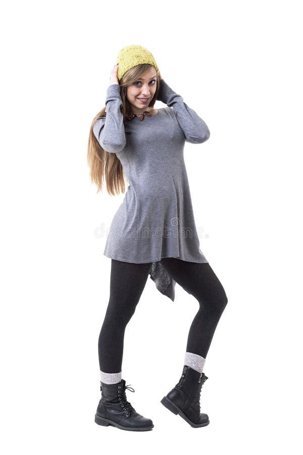 Jeune fille mignonne espiègle dans des vêtements élégants tenant la calotte et la pose jaunes photographie stock libre de droits