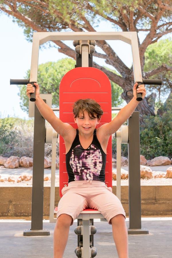 Jeune fille mignonne exerçant le corps supérieur sur la machine de gymnase dehors image libre de droits