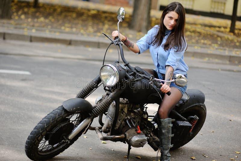 Jeune fille mignonne s'asseyant sur une grande moto photo stock