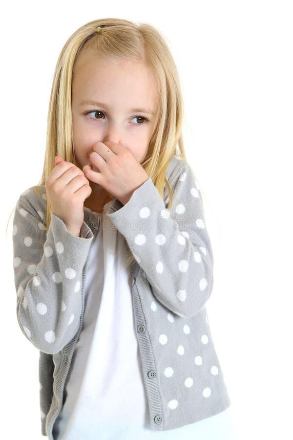 Jeune fille mignonne tenant son nez d'une mauvaise odeur image stock