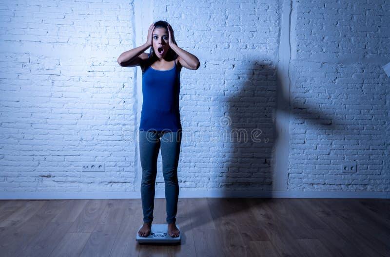 Jeune fille mince d'ajustement sur l'échelle hantée avec le gain de poids se sentant gros et désespéré images stock