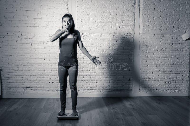 Jeune fille mince d'ajustement sur l'échelle hantée avec le gain de poids se sentant gros et désespéré photo libre de droits