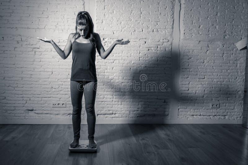 Jeune fille mince d'ajustement sur l'échelle hantée avec le gain de poids se sentant gros et désespéré image stock