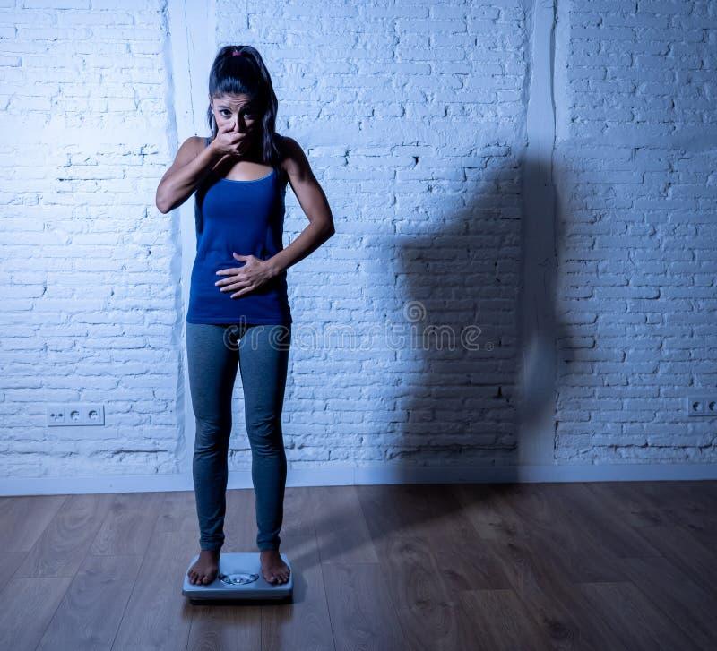 Jeune fille mince d'ajustement sur l'échelle hantée avec le gain de poids se sentant gros et désespéré image libre de droits