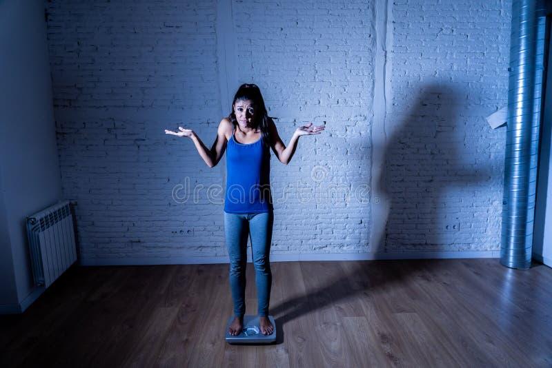 Jeune fille mince d'ajustement sur l'échelle hantée avec le gain de poids se sentant gros et désespéré photos libres de droits