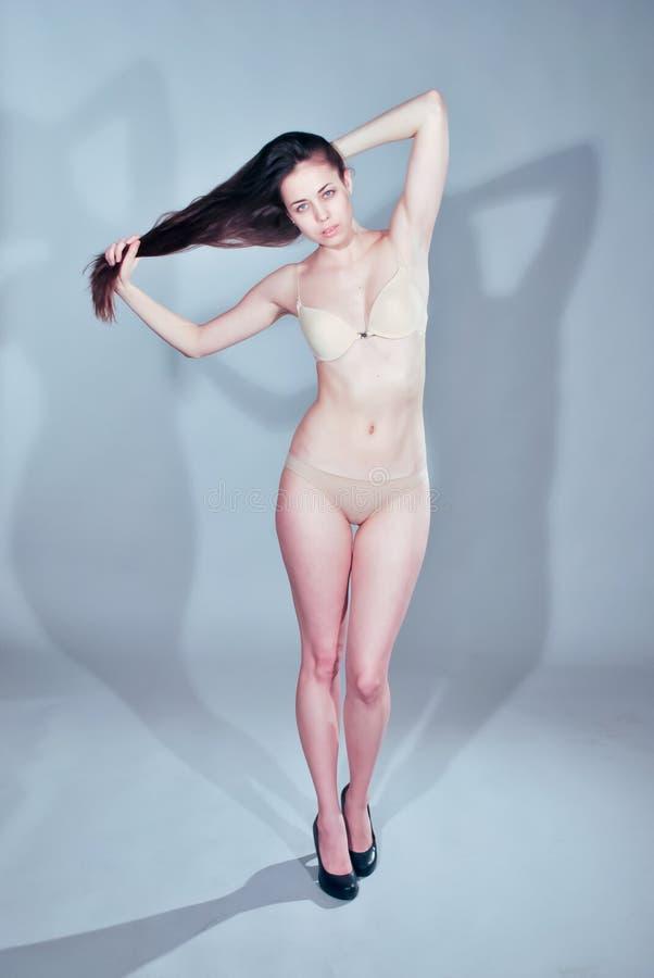Jeune fille modèle à la mode tenant des cheveux dans des mains image stock