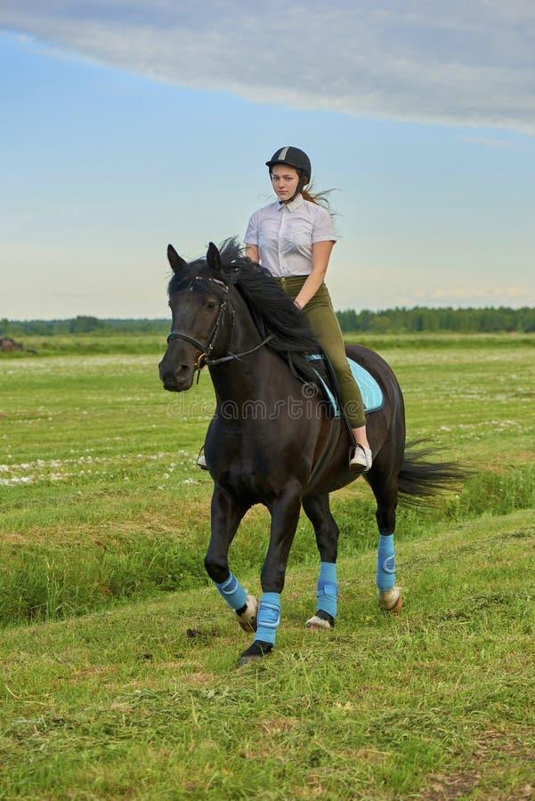 Jeune fille montant un cheval à travers le pays photos stock