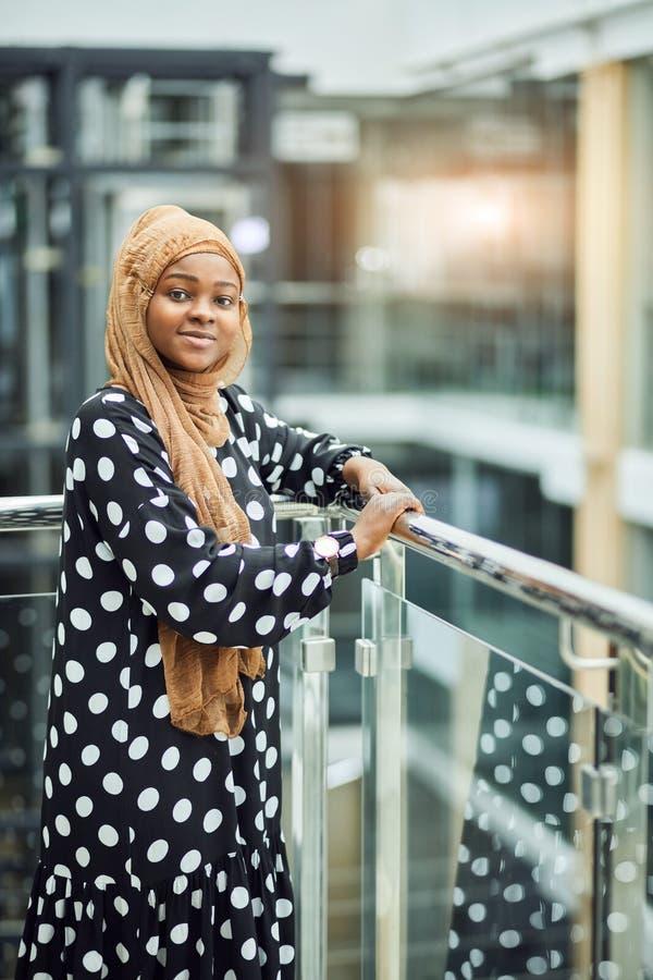 Jeune fille musulmane africaine attirante portant la robe élégante et le hijab en soie d'or images libres de droits