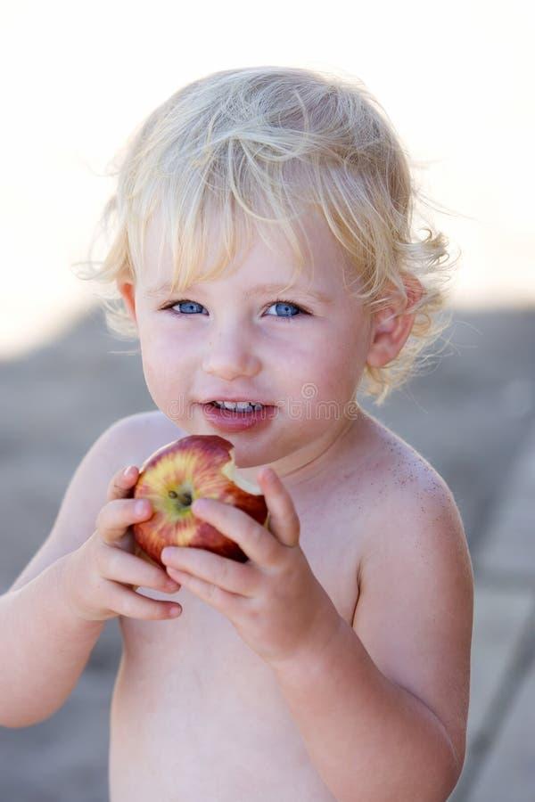 Jeune fille ou enfant en bas âge mangeant la pomme photos stock