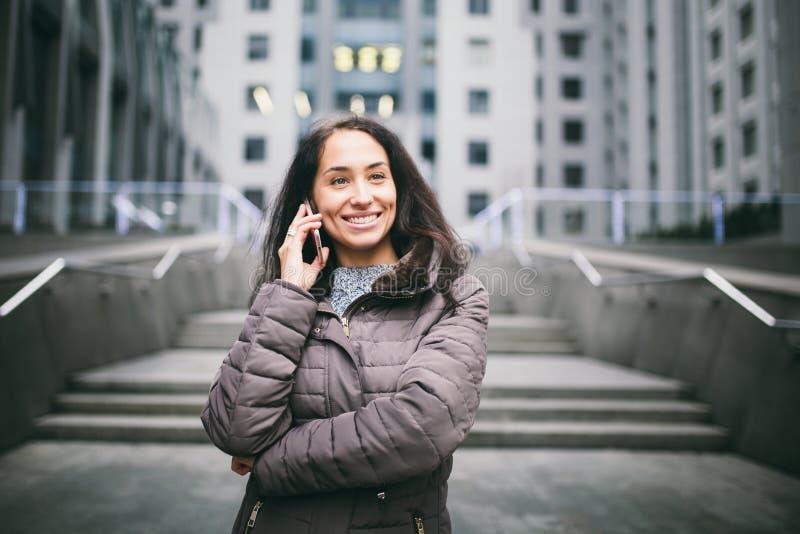 Jeune fille parlant au téléphone portable au centre d'affaires de cour la fille avec de longs cheveux foncés s'est habillée dans  photo stock