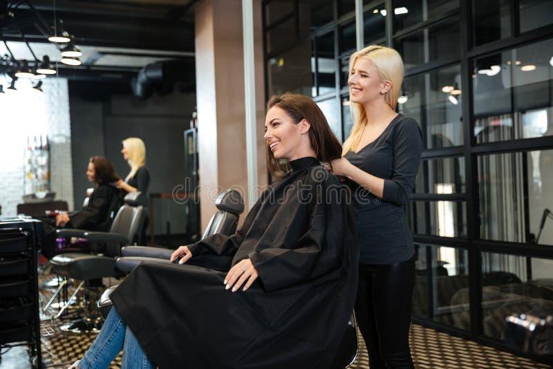 Jeune fille parlant avec le coiffeur dans le salon de beauté image libre de droits