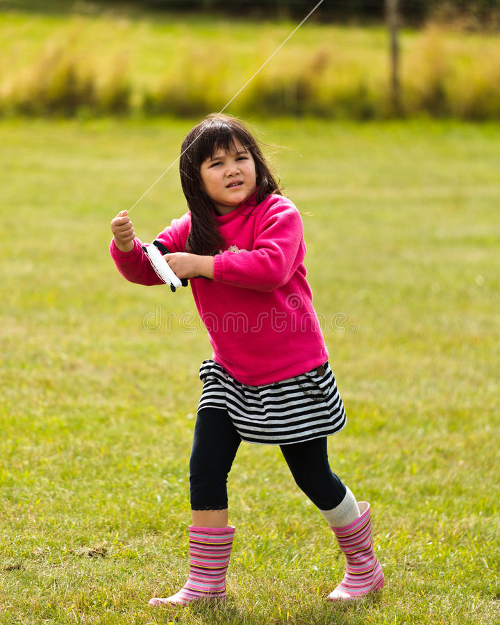 Jeune fille pilotant un cerf-volant photos stock