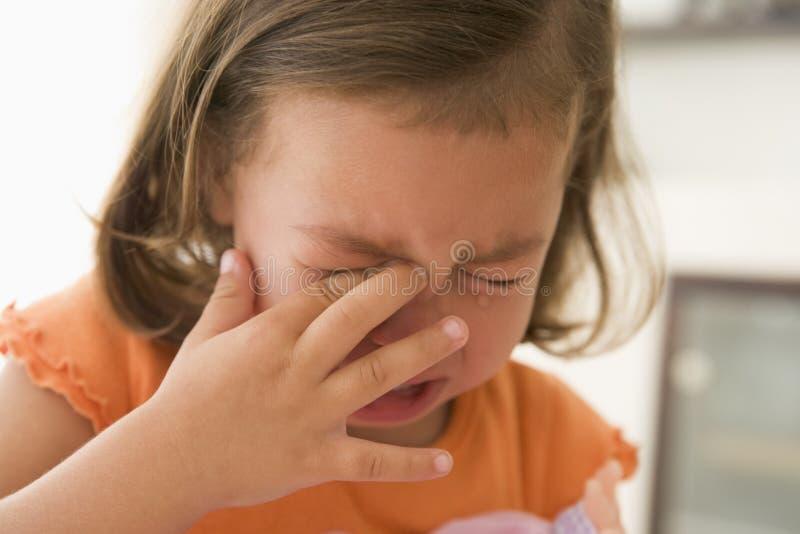 Jeune fille pleurant à l'intérieur image stock