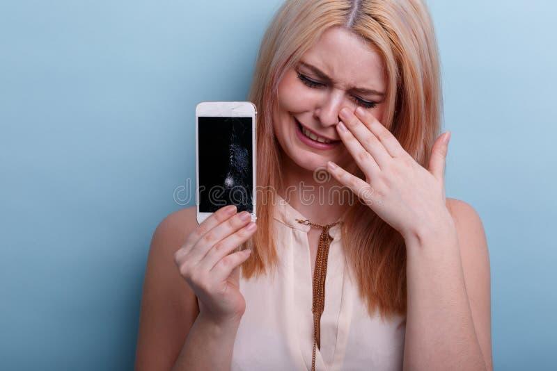 Jeune fille, pleurant jugeant un téléphone portable cassé disponible Plan rapproché Un déjeuner sec dans une cuillère image stock