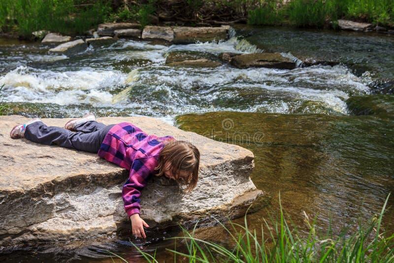 Jeune fille plongeant sa main dans l'eau photo stock