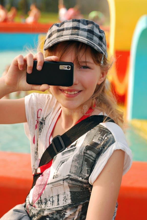 Jeune fille prenant la photo avec le téléphone portable photos stock