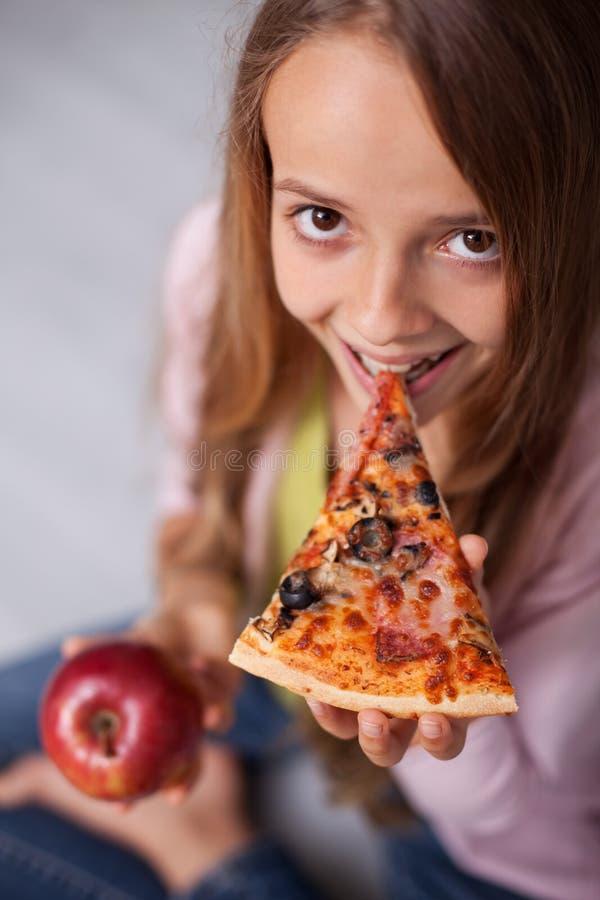 Jeune fille prenant une morsure d'une tranche de pizza conservant la pomme pour photos libres de droits