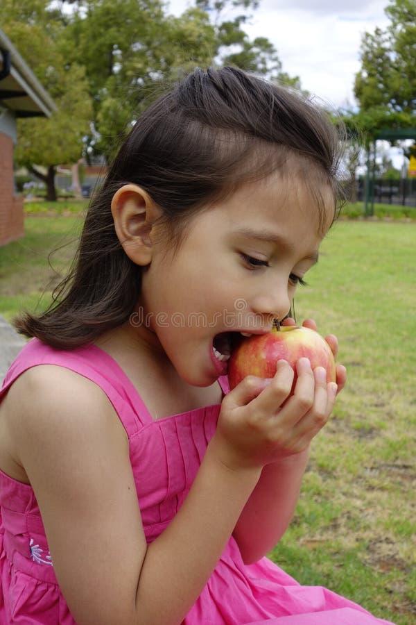 Jeune fille prenant une morsure de son Apple. photos stock