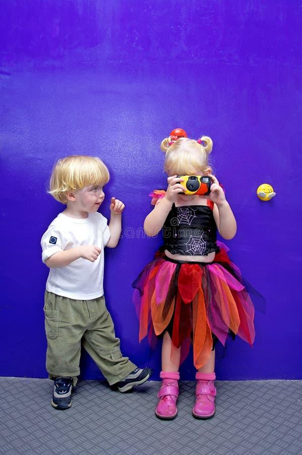 Jeune fille prenant une photo avec l'observation de petit garçon image libre de droits